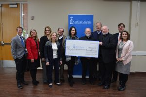 Msgr. Kevin Sullivan presents a check for disaster relief to Catholic Charities Galveston-Houston