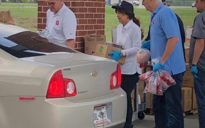 Volunteers loading food into cars at Mamie George Community Center